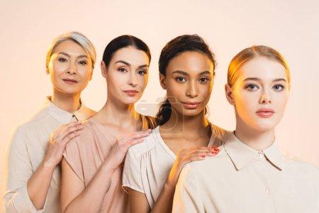 Photo pour Quatre belles femmes multiculturelles regardant une caméra isolée sur beige - image libre de droit