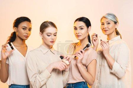 Photo pour Quatre femmes multiculturelles tenant des cosmétiques décoratifs isolés sur beige - image libre de droit