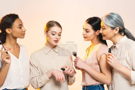 Photo for Attractive multicultural women holding decorative cosmetics isolated on beige - Royalty Free Image