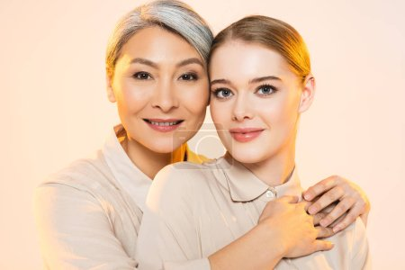 Photo for Two beautiful multicultural women with makeup looking at camera isolated on beige - Royalty Free Image