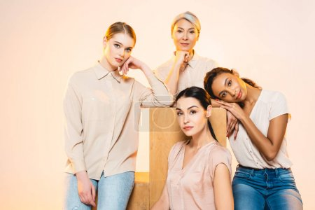 beautiful multicultural women with makeup looking at camera isolated on beige