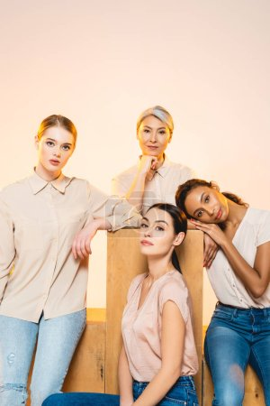 Photo for Four beautiful multicultural women with makeup looking at camera isolated on beige - Royalty Free Image