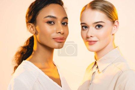 Foto de Dos atractivas mujeres multiculturales con maquillaje mirando a la cámara aislada en beige. - Imagen libre de derechos
