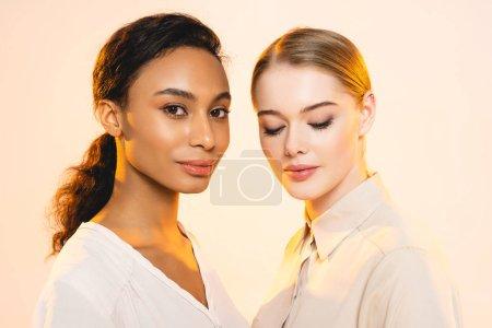 Photo pour Deux jolies femmes multiculturelles avec maquillage isolé sur beige - image libre de droit