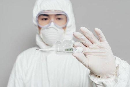 Photo pour Foyer sélectif de l'épidémiologiste asiatique tenant thermomètre montrant une température élevée isolé sur gris, prise panoramique - image libre de droit