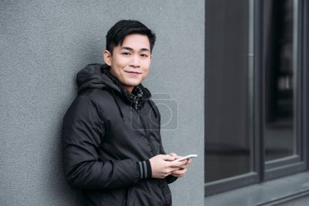 young asian man smiling at camera while standing by grey wall and chatting on smartphone