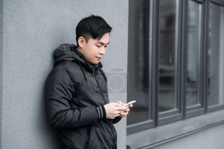 Photo for Young asian man chatting on smartphone while standing by grey wall - Royalty Free Image