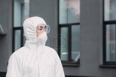 Photo for Asian epidemiologist in hazmat suit and respirator mask looking away while standing near building - Royalty Free Image