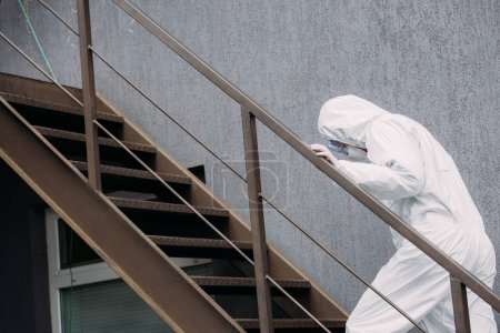 Photo for Asian epidemiologist in hazmat suit and respirator mask walking upstairs outside building - Royalty Free Image