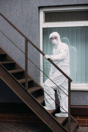 """Photo pour Épidémiologiste asiatique en combinaison de protection contre les matières dangereuses et masque de protection marchant à l """"étage extérieur du bâtiment - image libre de droit"""