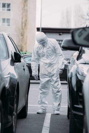 Photo for Selective focus of asian epidemiologist in hazmat suit and respirator mask inspecting vehicles on parking lot - Royalty Free Image