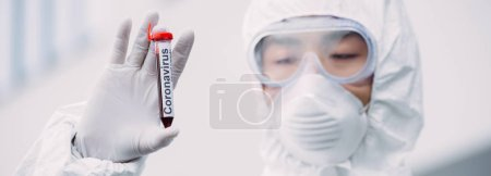 Photo for Panoramic shot of asian epidemiologist in hazmat suit and respirator mask looking at test tube with blood sample while standing outdoors - Royalty Free Image