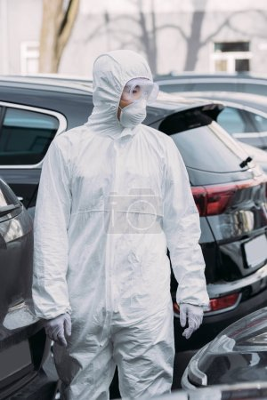 Photo for Asian epidemiologist in hazmat suit and respirator mask inspecting cars on parking lot - Royalty Free Image