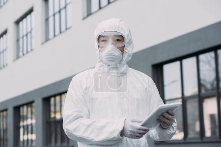 Photo for Asian epidemiologist in hazmat suit and respirator mask holding digital tablet and looking at camera while standing on street - Royalty Free Image