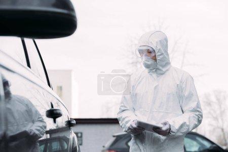 Foto de Enfoque selectivo de epidemiólogo asiático en traje de materiales peligrosos y máscara respiratoria celebración tableta digital mientras inspecciona vehículos en la calle - Imagen libre de derechos
