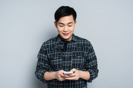 Photo for Young asian man smiling while using smartphone on grey background - Royalty Free Image