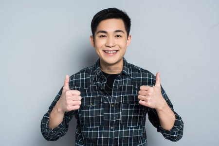 Photo for Smiling asian man looking at camera while showing thumbs up on grey background - Royalty Free Image
