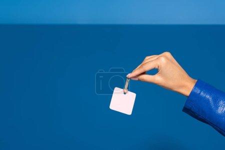 Photo pour Vue recadrée de femme afro-américaine tenant une étiquette vierge sur fond bleu - image libre de droit