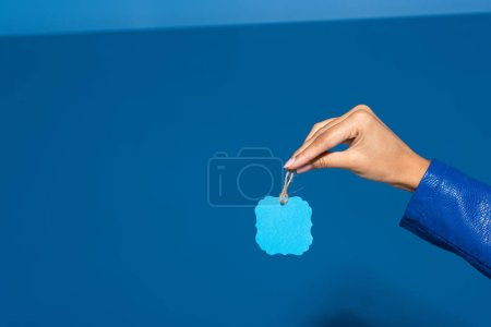 Photo for Cropped view of african american woman holding blank label on blue background - Royalty Free Image