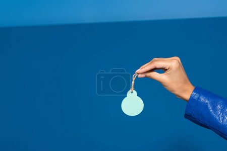 cropped view of african american woman holding blank label on blue background