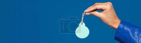 Photo pour Vue recadrée d'une femme afro-américaine tenant une étiquette vierge isolée sur une photo panoramique bleue - image libre de droit