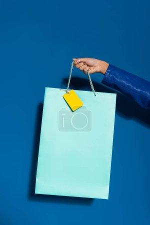 Photo pour Vue recadrée de femme afro-américaine tenant un sac à provisions avec étiquette vierge sur bleu - image libre de droit