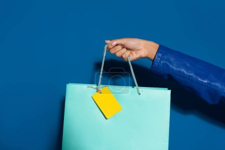 Photo pour Cropped view of african american woman holding shopping bag with blank label on blue - image libre de droit