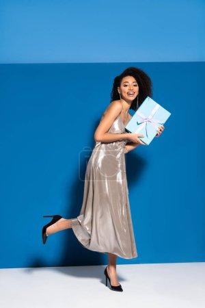 Photo pour Jolie américaine africaine en robe argentée posant avec cadeau sur fond bleu - image libre de droit