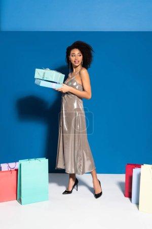 Photo pour Heureuse belle femme afro-américaine en robe d'argent tenant des boîtes-cadeaux près de sacs à provisions sur fond bleu - image libre de droit