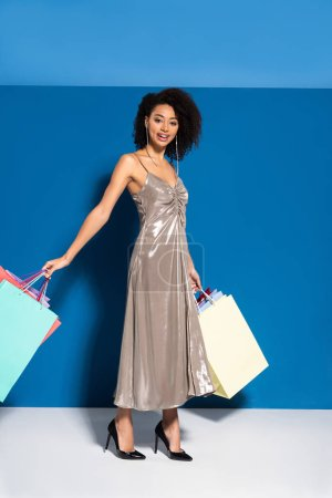 Photo pour Smiling elegant african american woman in silver dress holding shopping bags on blue background - image libre de droit