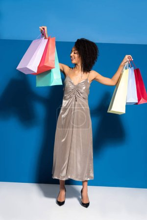 smiling elegant african american woman in silver dress looking at shopping bags on blue background