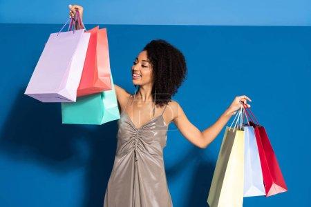 Photo pour Élégante femme africaine américaine souriante en robe d'argent regardant les sacs à provisions sur fond bleu - image libre de droit