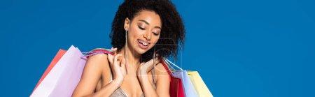 Foto de Sonriente mujer afriamericana elegante vestida de plata con bolsas de compras en fondo azul, tiro panorámico. - Imagen libre de derechos