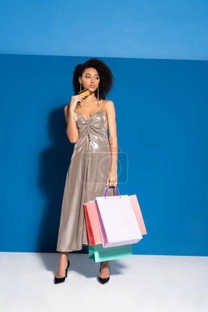 élégante femme afro-américaine en robe argentée tenant des sacs à provisions et carte de crédit sur fond bleu