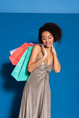 happy elegant african american woman in silver dress holding shopping bags on blue background