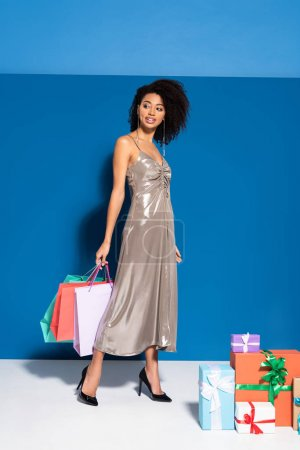 smiling beautiful african american woman in silver dress holding shopping bags near gifts on blue background