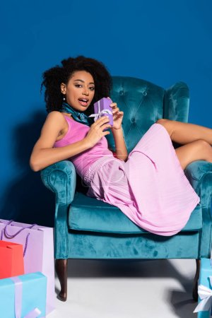 surprised african american woman sitting in velour armchair with gift box near purchases on blue background