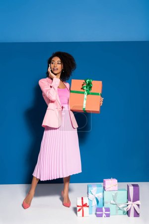 elegant smiling african american woman talking on smartphone near gifts on blue background