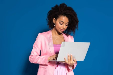Photo for Elegant african american businesswoman using laptop on blue background - Royalty Free Image