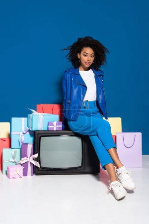 Photo for Smiling african american woman sitting on vintage television near gifts and shopping bags on blue background - Royalty Free Image