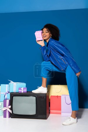 Photo for Smiling african american woman standing on vintage television with gift on blue background - Royalty Free Image