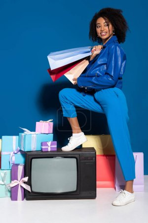 Photo for Smiling african american woman sitting on vintage television with shopping bags on blue background - Royalty Free Image