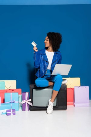 Photo for Smiling african american woman sitting on vintage television with laptop and credit card near gifts and shopping bags on blue background - Royalty Free Image