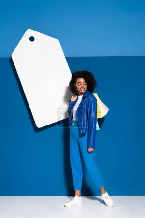 Photo for Smiling african american woman with shopping bags near big blank price tag on blue background - Royalty Free Image