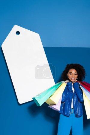 Photo pour Une Américaine d'origine africaine souriante avec des sacs à provisions près d'une grosse étiquette de prix vierge sur fond bleu - image libre de droit