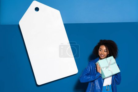 Photo for Smiling african american woman with gift near big blank price tag on blue background - Royalty Free Image