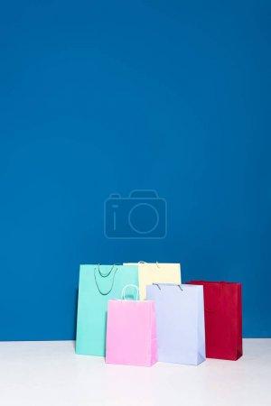 Photo pour Sacs à provisions en papier coloré sur fond bleu - image libre de droit