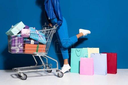 Photo pour Vue recadrée de femme afro-américaine avec panier plein de cadeaux près des sacs à provisions sur fond bleu - image libre de droit