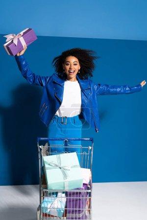 heureuse femme afro-américaine avec panier plein de cadeaux sur fond bleu