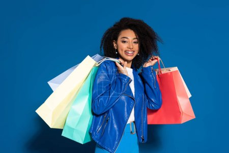 Photo pour Une Américaine d'origine africaine souriante avec des sacs à provisions sur fond bleu - image libre de droit